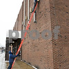 012417  Wesley Bunnell | Staff<br /> <br /> CMHA workers change the outside bulbs into 227 Main St which was recently purchased.