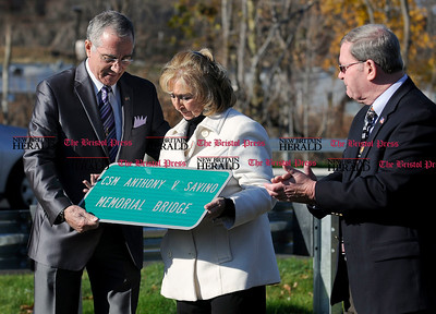 11/19/2011 Mike Orazzi | Staff State Rep. Frank Nicastro presents with a CSM Anthony V. Savino's wife Deanna Savino with a duplicate sign during a ceremony naming the Pequabuck River bridge on the Route 72 extension on Saturday morning. On the right is Bristol Mayor Art Ward.  ** for a Steve story **