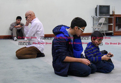 012717  Wesley Bunnell | Staff  Brothers Baheer Akberzai, middle, and Zain Akberzai, right, play games as a man kneels in prayer just before afternoon prayer at the Berlin Mosque on Friday Jan 27.
