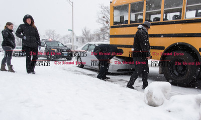 013117 Wesley Bunnell | Staff  An accident involving a Honda Civic and a school bus occurred at the intersection of Arch and Monroe St on Tuesday afternoon.  Ofc. Wichowski looks over the damage as Vance School Principal Sarah Harris , second from the left, walks to speak with the bus driver.
