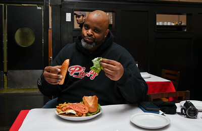 010316  Wesley Bunnell | Staff  Food reviewer Daymon Patterson, aka Daym Drops, reviewed a new sandwich at Grand Pizza in New Britain on Tuesday afternoon. The sandwich named Tommy's Big Boy Burger was quickly renamed the Daym Drop Savage Burger by Patterson. Patterson jokingly takes the lettuce from his sandwich as owner Tommy Qoku looks over his shoulder.
