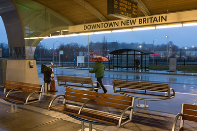 010316  Wesley Bunnell | Staff  A rider at the Downtown New Britain CTfastrak exits from the station into the rain f the rain on a cold and rainy Tuesday afternoon.