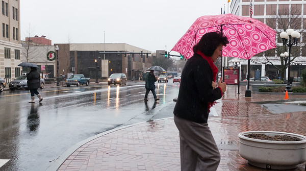 010316  Wesley Bunnell | Staff  Pedestrians cross West Main St. in front of City Hall on a cold and rainy Tuesday afternoon in downtown New Britain.