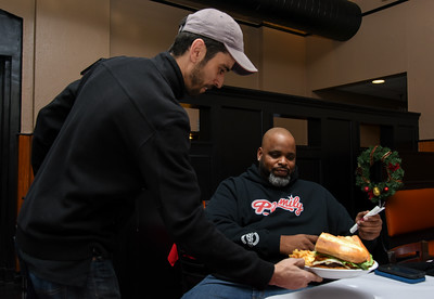 010316  Wesley Bunnell | Staff  Food reviewer Daymon Patterson, aka Daym Drops, reviewed a new sandwich at Grand Pizza in New Britain on Tuesday afternoon. The sandwich named Tommy's Big Boy Burger was quickly renamed the Daym Drop Savage Burger by Patterson.  Owner Tommy Qoku delivers the burgers to Patterson at his table.
