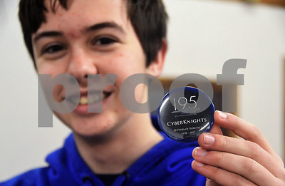 1/4/2017 Mike Orazzi | Staff Southington Cyber Knights robotics team member Mike Jagos holds a button he designed for the team at their new location on West Street in Southington.