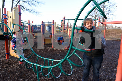 010416  Wesley Bunnell | Staff  A mild afternoon brought Amanda Capo and her twins Logan and Sofia to Walnut Hill Park's playground on Wednesday.  Amanda helps Logan across an obstacle course as Sofia waits her turn.