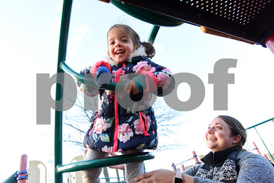 010416  Wesley Bunnell | Staff  A mild afternoon brought Amanda Capo and her twins Logan and Sofia to Walnut Hill Park's playground on Wednesday.  Sofia climbs up onto a playscape while mom Amanda keeps an eye on her.