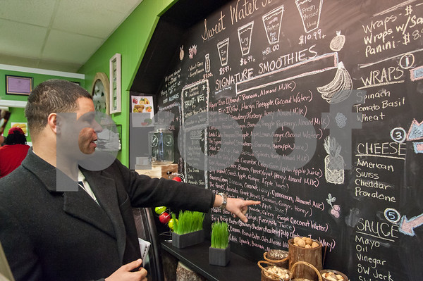 01/16/18 Wesley Bunnell | Staff The official ribbon cutting for Sweetwater Juice Bar & Deli located at 60 West Main St. was held on Tuesday afternoon. Alderman Kristian Rosado looks over the menu.