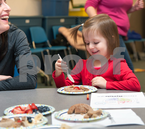 01/24/18 Wesley Bunnell   Staff Registered Dietitian Katie Shepherd brought her Food Explorers program to the Bristol Public Library on Wednesday morning to work with a group of pre school age children. The program teaches healthy food choices through sensory experiences and activities followed with hands on food exploration. Bukuroshe Belieri, L, sits with daughter Emma, age 3, as she enjoys her plate of food towards the end of the program.