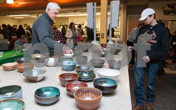 01/31/18 Wesley Bunnell | Staff The Friendship Service Center held their first ever Souper Bowl at E.C. Goodwin on Wednesday evening to raise awareness of hunger and provide funding their soup kitchen. Guests were able to buy a handcrafted ceramic bowl made by Central Connecticut State University art students as the entrance fee and have it filled with the soup of their choice. Students from E.C. Goodwins culinary department handled the serving of the soups. Carl Krein, L, looks over the bowls available for purchase with Adam Young, V.P. of the National Honor Society, standing on the other side of the table doing the same.
