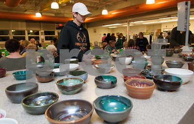 "01/31/18  Wesley Bunnell | Staff  The Friendship Service Center held their first ever ""Souper Bowl"" at E.C. Goodwin on Wednesday evening to raise awareness of hunger and provide funding their soup kitchen. Guests were able to buy a handcrafted ceramic bowl made by Central Connecticut State University art students as the entrance fee and have it filled with the soup of their choice. Students from E.C. Goodwin's culinary department handled the serving of the soups. Adam Young, V.P. of the National Honor Society, looks over the bowls available after spending the evening volunteering and looking over the tables."