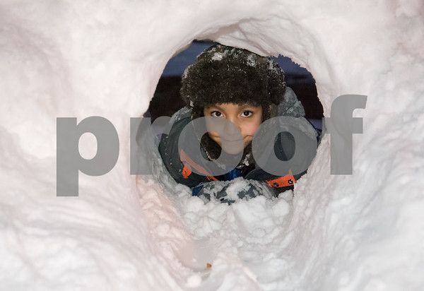 01/10/18 Wesley Bunnell | Staff Kishon Lewis, age 7 , peeks through a tunnel made in the snow in Central Park on Wednesday as he plays with family and friends.