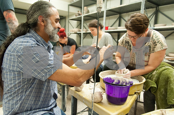 01/10/18 Wesley Bunnell | Staff Volunteers gathered at CCSU on Wednesday evening to throw clay for bowls which will eventually be decorated and sold to benefit the Friendship Center's soup kitchen in an event called the Souper Bowl. CCSU Professor Vicente Garcia , L, uses Facebook Live to show the process.