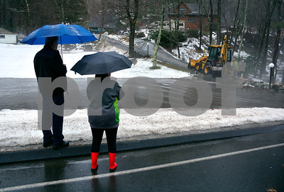 1/12/2018 Mike Orazzi   Staff Plymouth residents Rich Blair and Sherry Kizzia watch as a crew from public works opens a drain causing a flooding issue on Old Waterbury Road during Friday's rain storm.