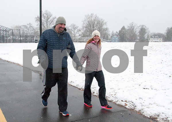 01/17/18 Wesley Bunnell | Staff Dave and Jennifer Bosso hold hands as they walk through Walnut Hill Park on Wednesday after a storm spread several inches of snow starting earlier that morning.