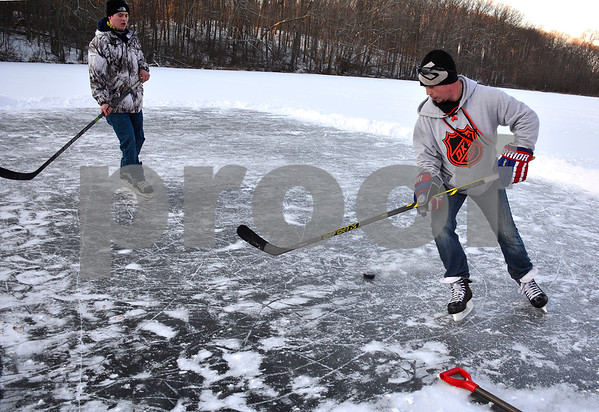 1/18/2018 Mike Orazzi | Staff John Venditti and Jay Fortin while playing ice hockey on Birge Pond in Bristol Thursday afternoon.