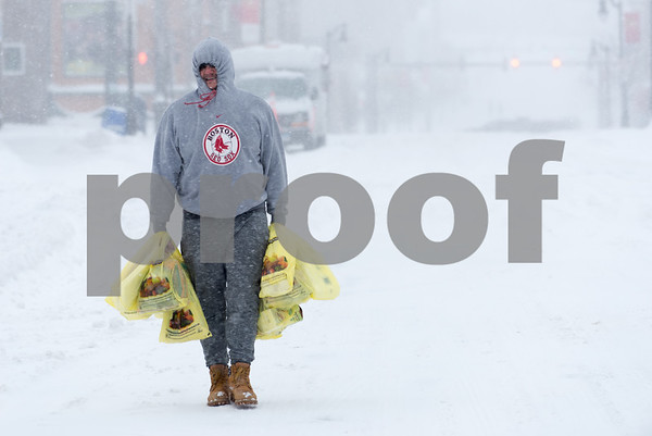 01/04/18 Wesley Bunnell | Staff A blizzard featuring high winds and causing icy conditions hit CT throughout the day on Thursday. Josh Morales makes his way with arms full of groceries up Broad St where it was easier to walk due to un shoveled sidewalks.