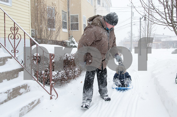 01/04/18 Wesley Bunnell | Staff A blizzard featuring high winds and causing icy conditions hit CT throughout the day on Thursday. Robert Starzysna pulls his son David, age 3, on a sled on Broad St during the storm.