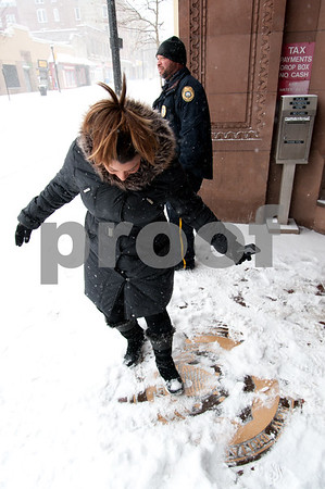 01/04/18 Wesley Bunnell | Staff A blizzard featuring high winds and causing icy conditions hit CT throughout the day on Thursday. Mayor Erin Stewart clears snow off of the town seal in front of city hall just before a Facebook live update about the conditions of the city during the storm.