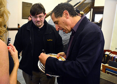 10/11/2014 Mike Orazzi | Staff The Simpsons producer Mike Reiss signs a clock for fan Addison Dittman during a visit to the Bristol Public Library on Saturday. Reiss had a section of the library dedicated to him during a short ceremony.