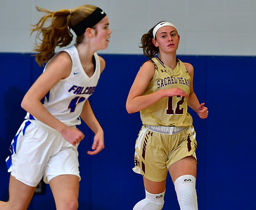1/2/2019 Mike Orazzi | Staff St. Paul Catholic High School's Olivia Heslin (4) and Sacred Heart's Hayley Tucker (12)during Wednesday night's girls basketball game in Bristol.