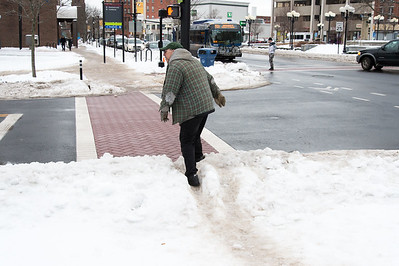 01/23/19  Wesley Bunnell | Staff  Several streets and sidewalks still remain covered in snow and ice on Wednesday after a weekend storm.  A pedestrian climbs over a mound of snow at an uncleared section of sidewalk at the intersection of Main St and Bank St.