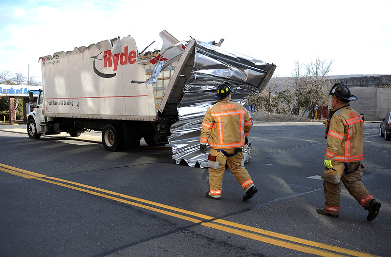 3/26/2014 Mike Orazzi   Staff Bristol firefighters check out damage to a box truck after the top was sheered off as the driver drove under the railroad under pass on Main Street Wednesday afternoon.