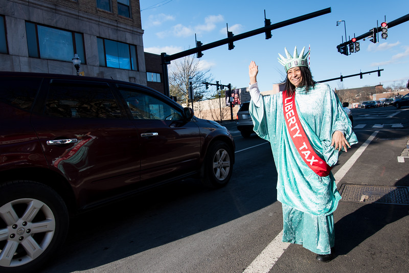 01/03/19  Wesley Bunnell | Staff  Luz Torres dressed as lady liberty waves to traffic passing by the  Liberty Tax Service location at 291 Main St on Thursday afternoon.