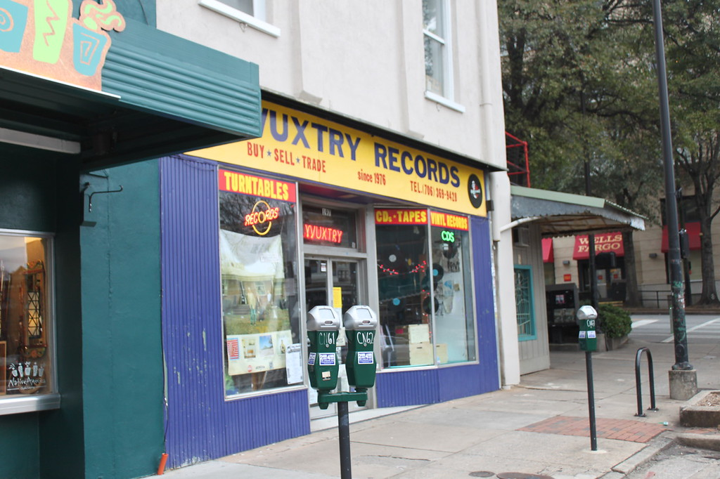Yellow and purple sign in front of a record store