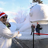 """Dick Bartz, of East Bethel, grins Saturday, Jan. 4, 2020, as he pushes a remote control button activating a smoke machine in the head of a whale snow sculpture, making it look like a blow hole. Bartz is the self-proclaimed """"crazy uncle"""" of the Bartz brothers -- Austin, 25, Trevor, 24, and Connor, 21 -- who build huge sea-themed snow sculptures in their family's front yard in Arden Hills every year. The brothers hope to raise $50,000 for clean water in third world countries. This is their ninth sculpture. The whale is available to view for free through Feb. 6. (Deanna Weniger / Pioneer Press)"""
