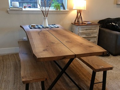 Boards from an oak burned by the Camp Fire have become a dining room table at Cody Anderson's hand. (Laura Urseny -- Enterprise-Record)