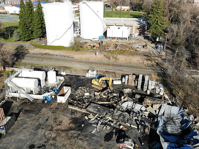 A tractor cleans up the charred remains of a fuel warehouse Thursday off of Nord Avenue in Chico. (Matt Bates -- Enterprise-Record)