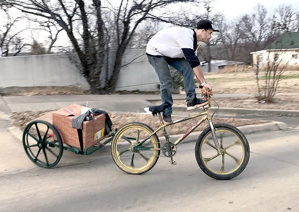 KEVIN HARVISON | Staff photo<br /> An unidentified man makes his way on to South Second Street from the McAlester Public Library in style as he had fun trick riding his bike down the hill.