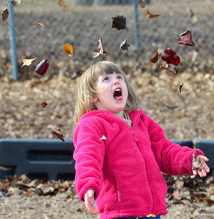 KEVIN HARVISON | Staff photo<br /> Chloe Myatt watches as leaves fall from the sky like snow flakes.