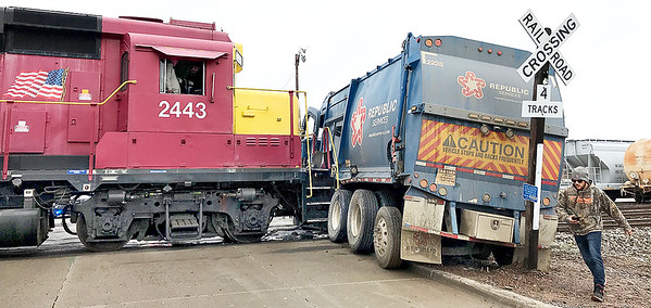 KEVIN HARVISON |<br /> A Republic Service trash truck and an Arkansas-Oklahoma Railroad collided around 11 a.m. Thursday were the railroad crosses S. D Street. No injuries were reported. Hydrolic fluid from the truck was spilled during the along the railroad tracks.