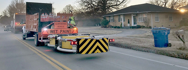 KEVIN HARVISON | Staff photo<br /> The sun sets on a road crew on South Nineth Street as the crew prepares several roads in McAlester to be striped and painted.