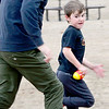 KEVIN HARVISON | Staff photo<br /> Pictured from left, Ben Webster chases his son Blake Webster as he looks back during  a quick game of football during a stop at Chadick Park before heading back to their home in Joplin, Mo.