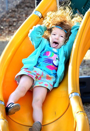 KEVIN HARVISON | Staff photo<br /> Sophie Foster enjoys the weather and a trip down a slide.
