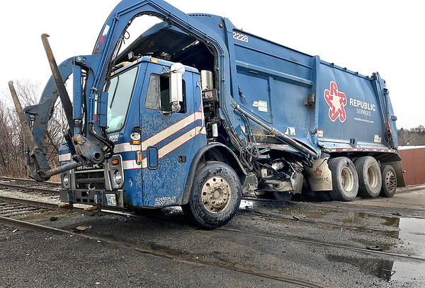 KEVIN HARVISON  <br /> A Republic Service trash truck sits on the railroad tracks after an Arkansas-Oklahoma Railroad engine collided around 11 a.m. Thursday were the railroad crosses S. D Street. No injuries were reported. Hydrolic fluid from the truck was spilled during the along the railroad tracks.