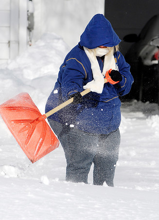 THB photo/John P. Cleary<br /> Kelli Allen was bundled up good to protect herself against the bitter cold temperatures and strong winds as she dug out from her home along west 38th Street in Anderson Monday.