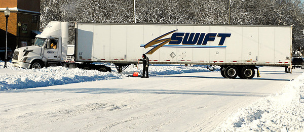 THB photo/John P. Cleary<br /> The driver of this semi tries to back out of its tracks after some shoveling was done after getting stuck along University Blvd. turning in to make a delivery blocking all lanes of traffic.