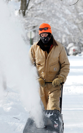 THB photo/John P. Cleary<br /> people working outside to clean off the snow had to bundle up against the bitter cold like this man cleaning a driveway in Pendleton.