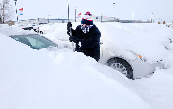 Don Knight / The Herald Bulletin<br /> Bill Jackson clears snow from a car as the sales team at Myers Autoworld works to clear the lot of snow on Tuesday.