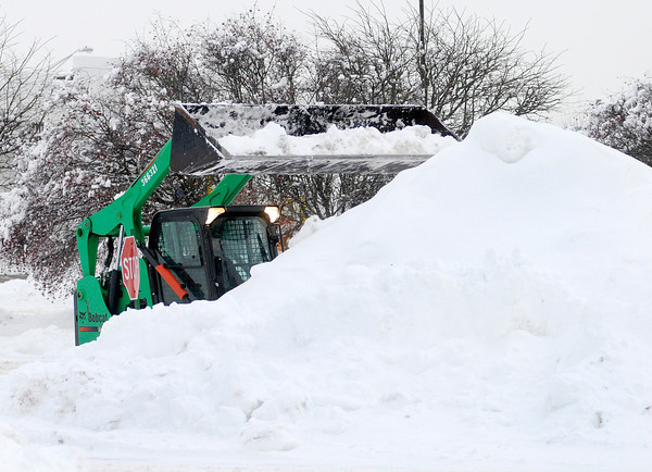 Don Knight / The Herald Bulletin<br /> A Bobcat piles up snow in the Applewood Center parking lot on Wednesday. Warmer temperatures forecast for the rest of the week will begin to thaw Madison County but a possibility of rain Saturday is raising concerns of flooding.