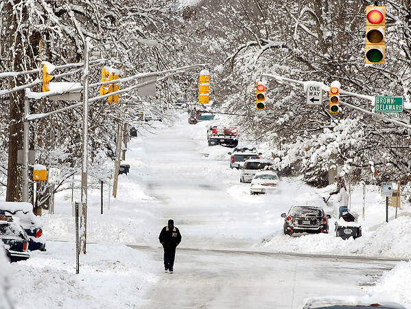 THB photo/John P. Cleary<br /> With cars still snowed in and and the roads still snow-packed and icy this man walks toward town along West 10th Street Wednesday morning.  As temperatures rise the next several days, and rain in the forecast, flooding may be a concern as the foot of snow that fell melts away.