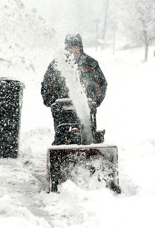 THB photo/John P. Cleary<br /> Stephen Turner uses a large snow blower to handle the volume of wet snow Sunday as he cleans off the area in front of his and his neighbors house on south Water Street in Chesterfield.