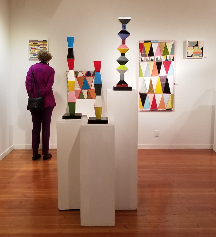 . AURA WHITTAKER for the Willits News A guest takes a closer look at Darrell Carpenter�s geometric collages during the opening Jan. 6.