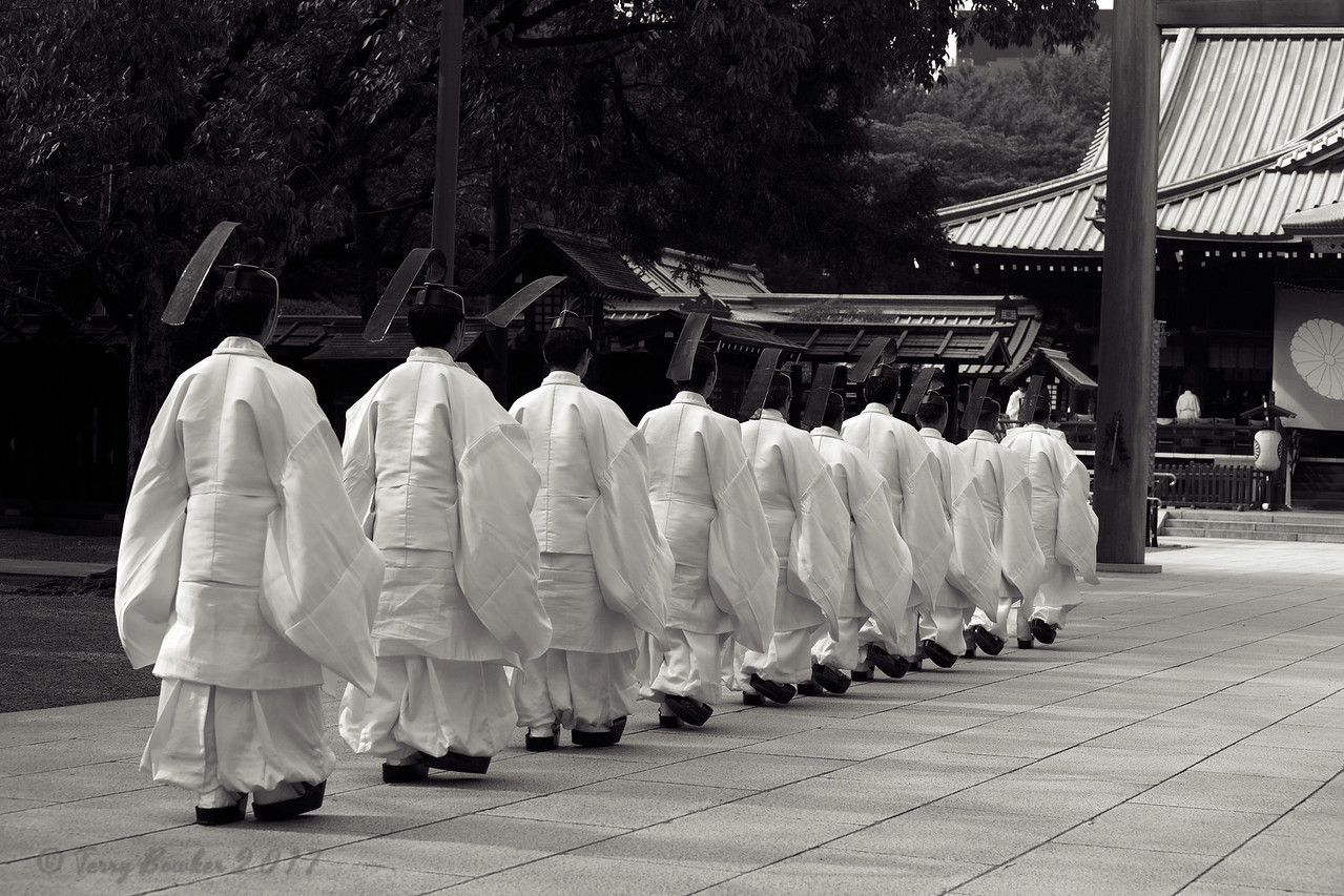 "Shinto priests walk to Torii gate before they administer a Shinto rite ""Kiyoharai"""