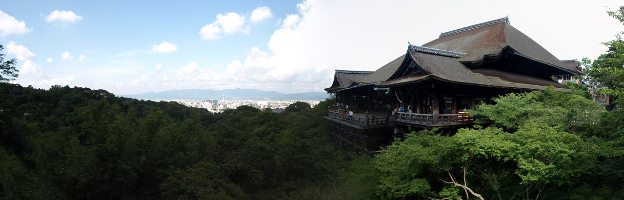 Another panoramic view of the Kiyomizu-Dera main hall. Note the tiny, distant spire of the Kyoto Tower silhouetted by the mountains behind it.