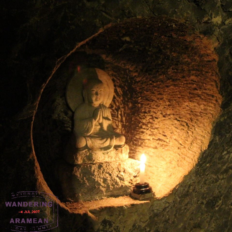 Candle illuminating one of the carved sculptures inside Hasedera's Benten-kutsu Cave